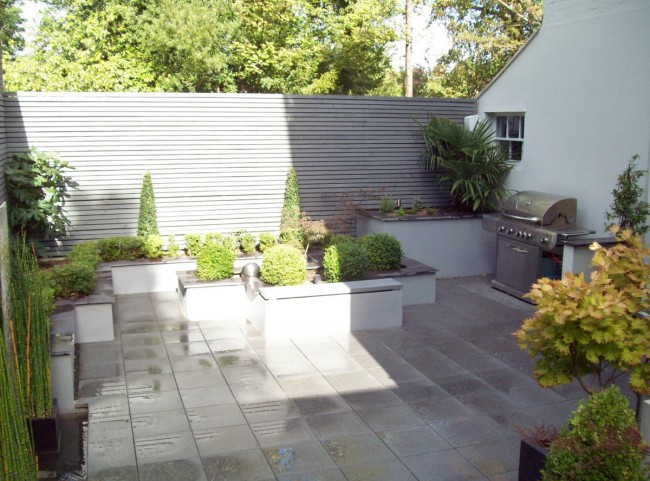 Courtyard garden with raised borders and painted slatted trellis