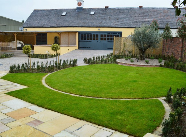 Courtyard garden with circular lawn with olive tree
