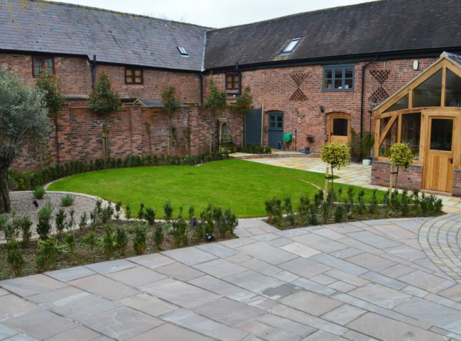 Courtyard garden with natural stone paving and circular lawn