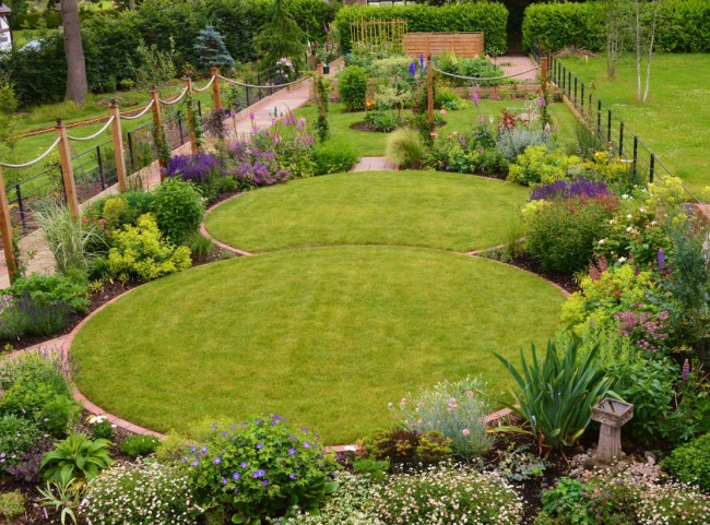 Circular lawns and traditional planting. Timber posts support ropes on to which roses and clematis will climb.