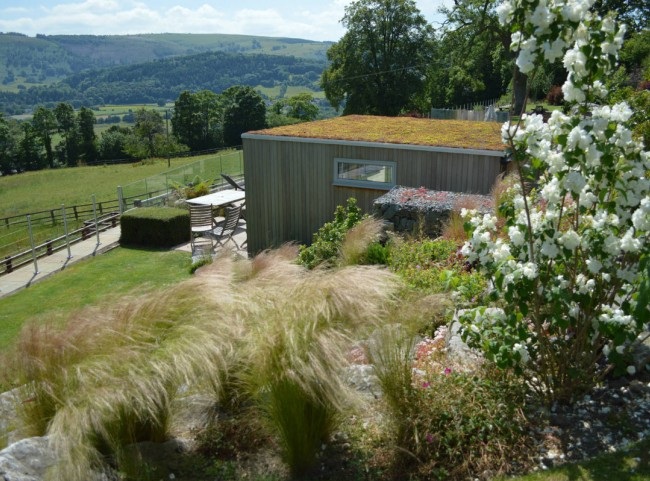 Terraced garden with boulders, grasses and garden room