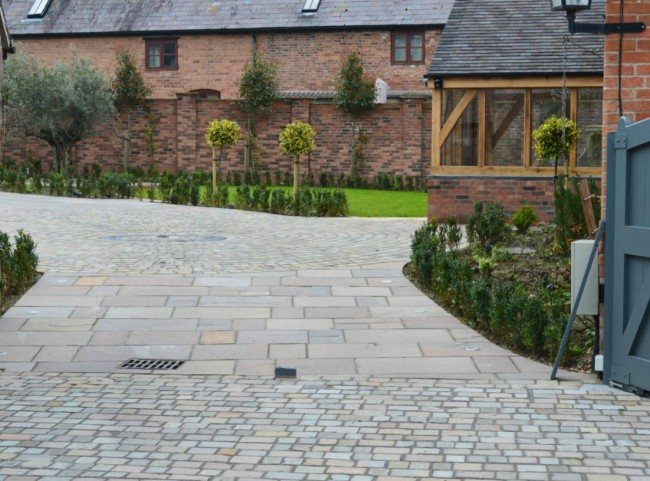 Courtyard garden with natural stone paving and cobble driveway