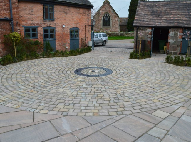 Courtyard garden with circular cobble driveway with drive-over water feature