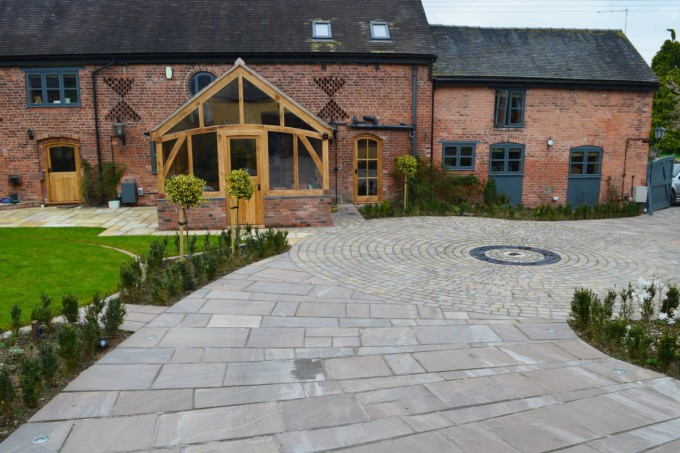Courtyard garden with natural stone paving and circular cobbled detail